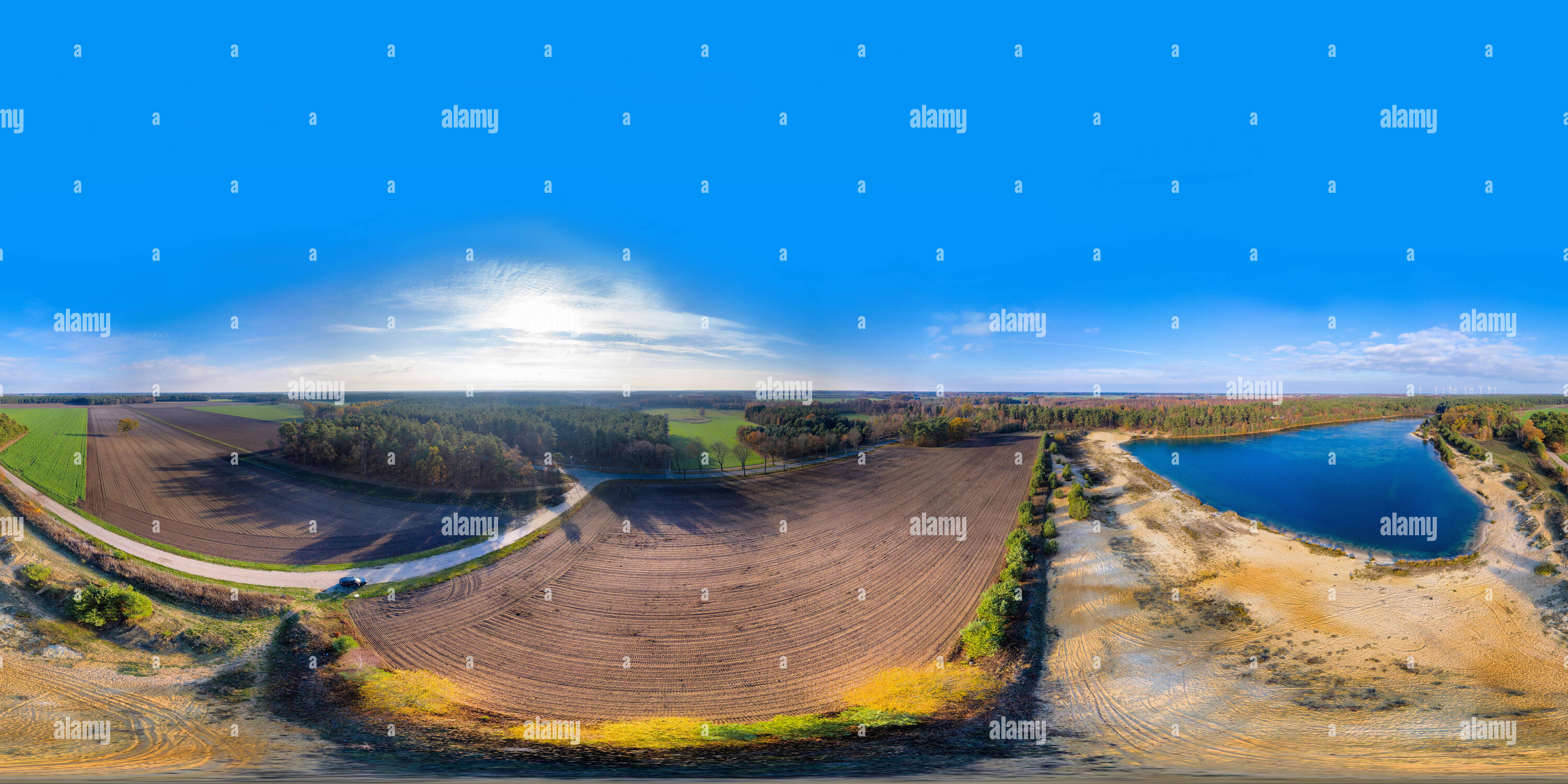 360 degree panoramic view of 360-degree panorama of a field and a gravel pond next to a forest and a country road, taken with the drone in flight