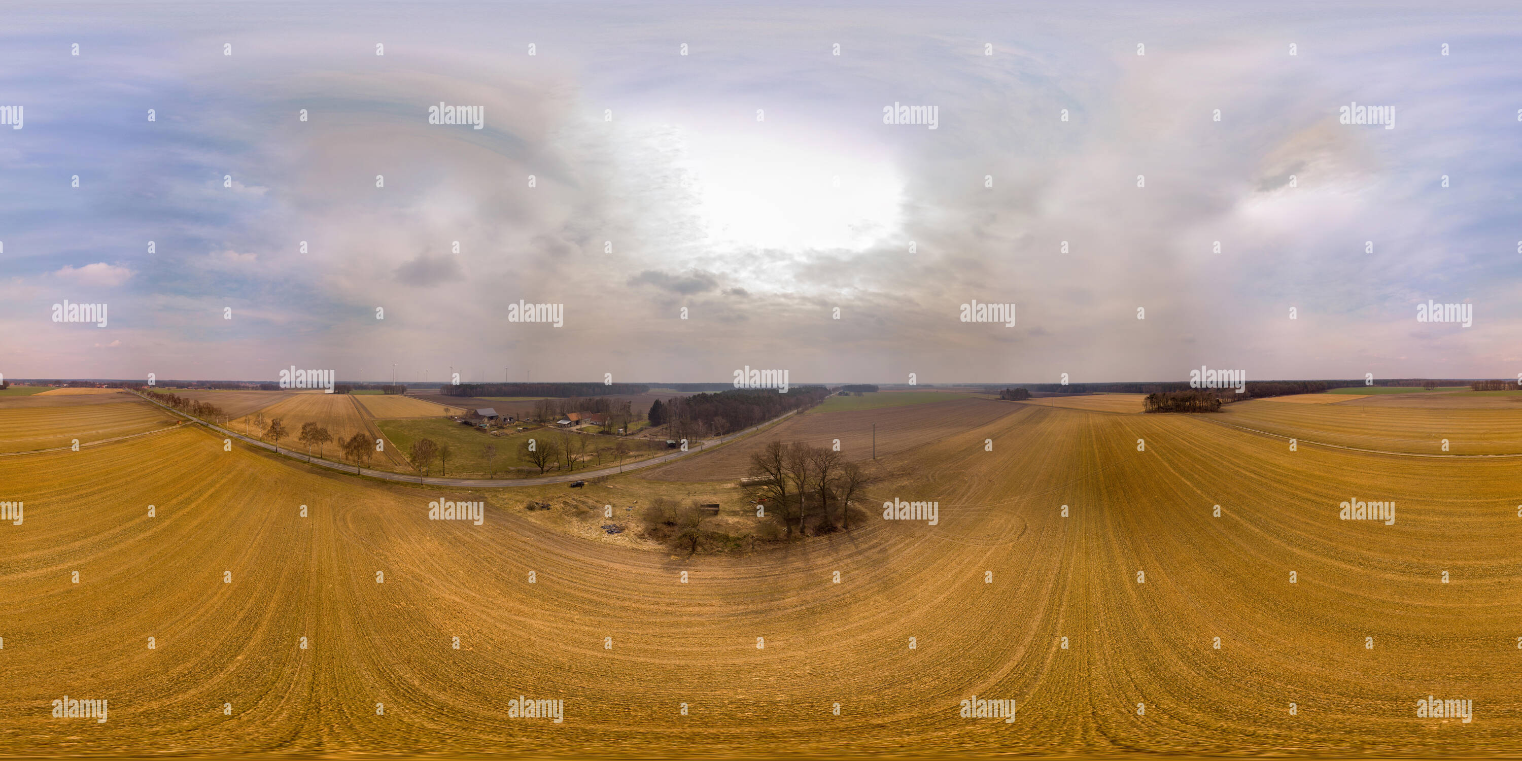 360-degree overview of a harvested field in the lowlands of northern Germany with a farm in the background and windmills on the horizon. - Stock Image