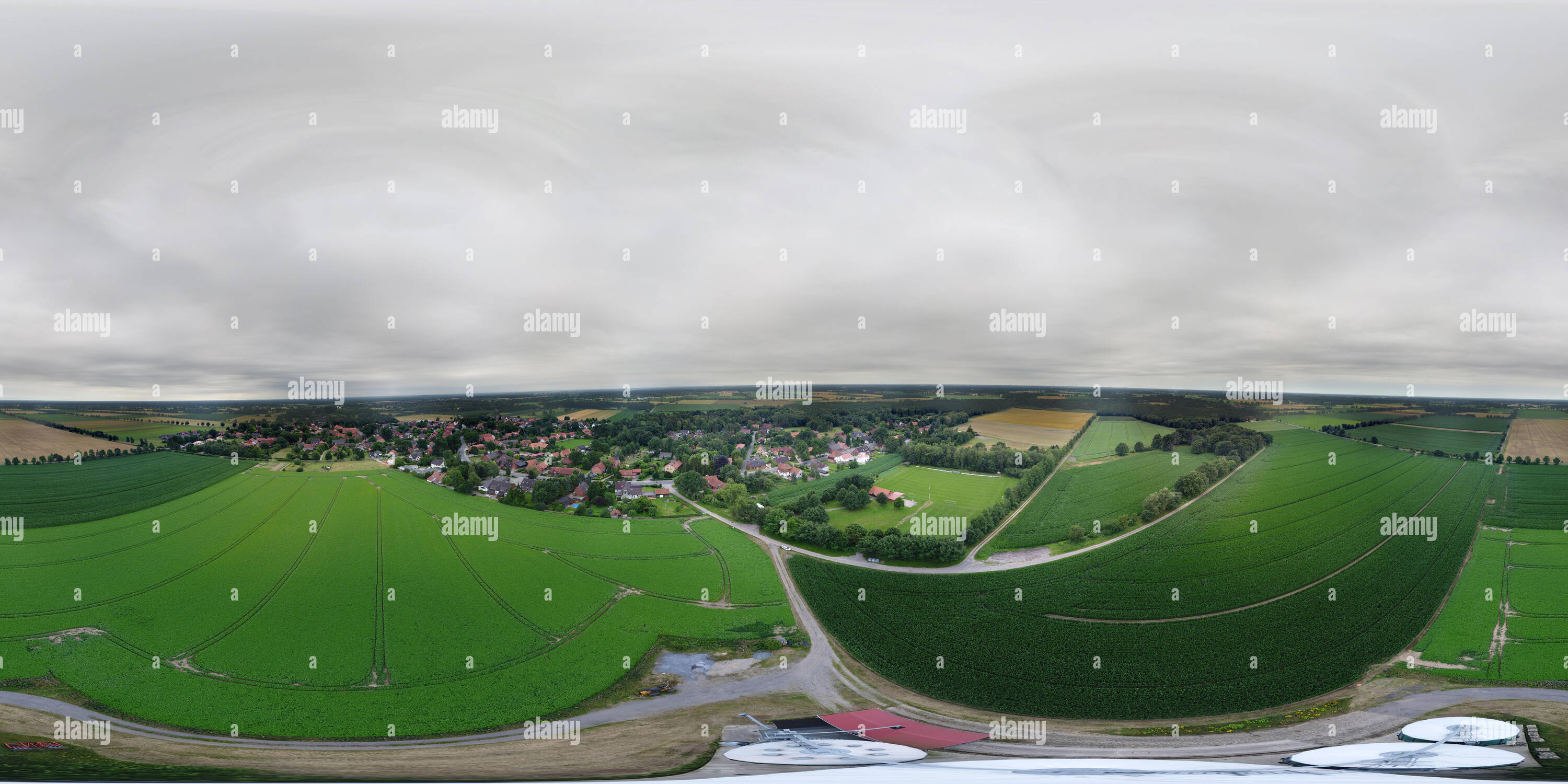 Spherical panorama of green fields behind a village and silos for grain in the foreground in vertical perspective, lowlands in Northern Germany - Stock Image