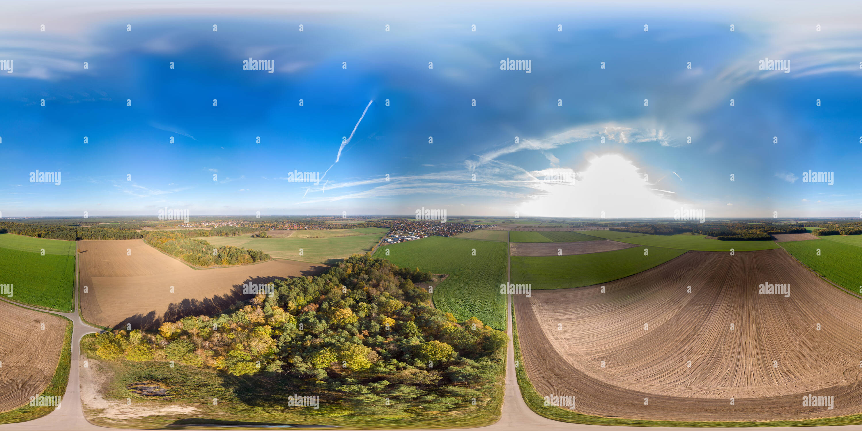 Panoramic view over a flat agricultural area in northern Germany with a small forest and two villages in the background. - Stock Image