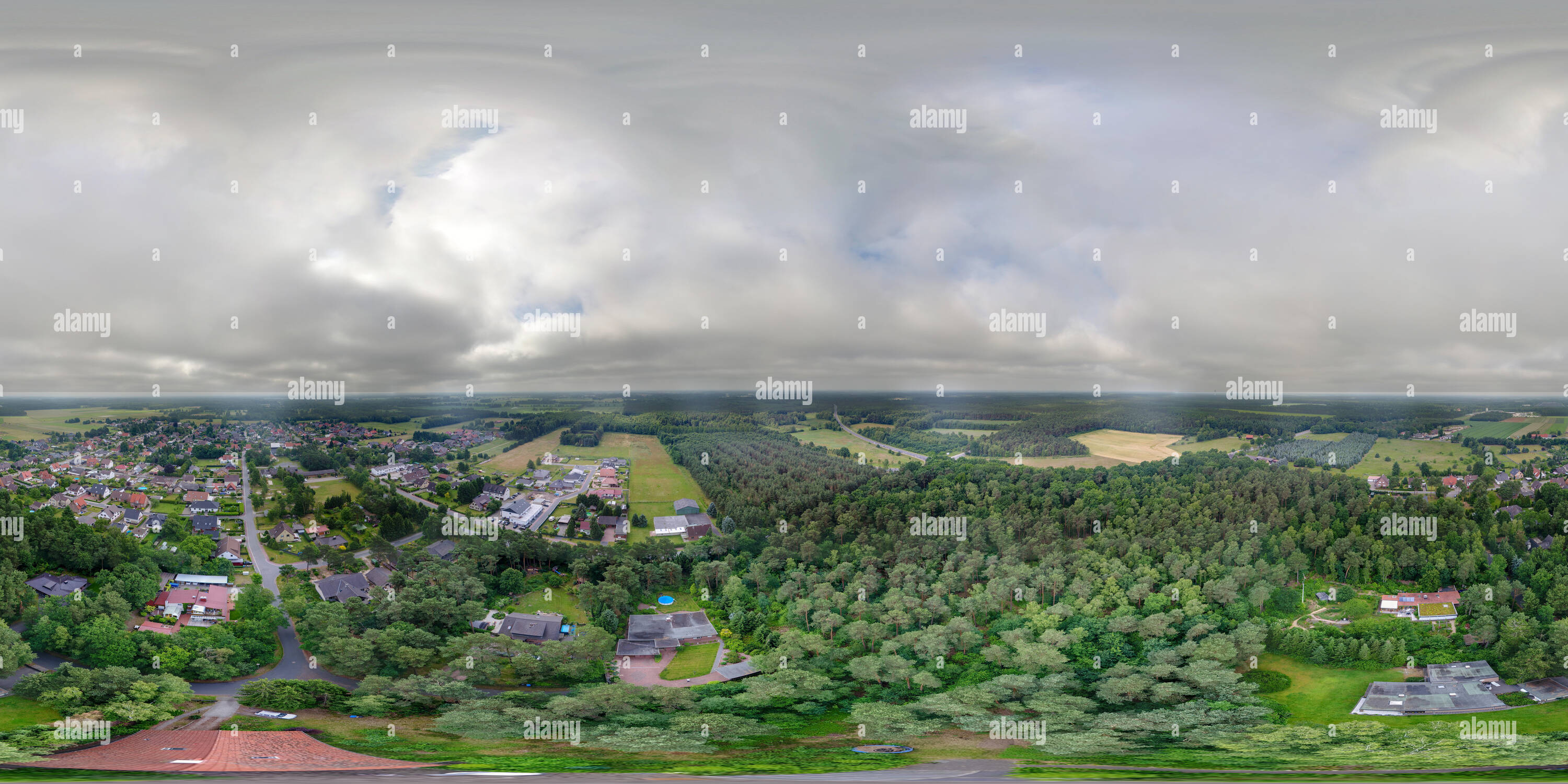3D Aerial view of a small detached house in an forest at the edge of a small village - Stock Image