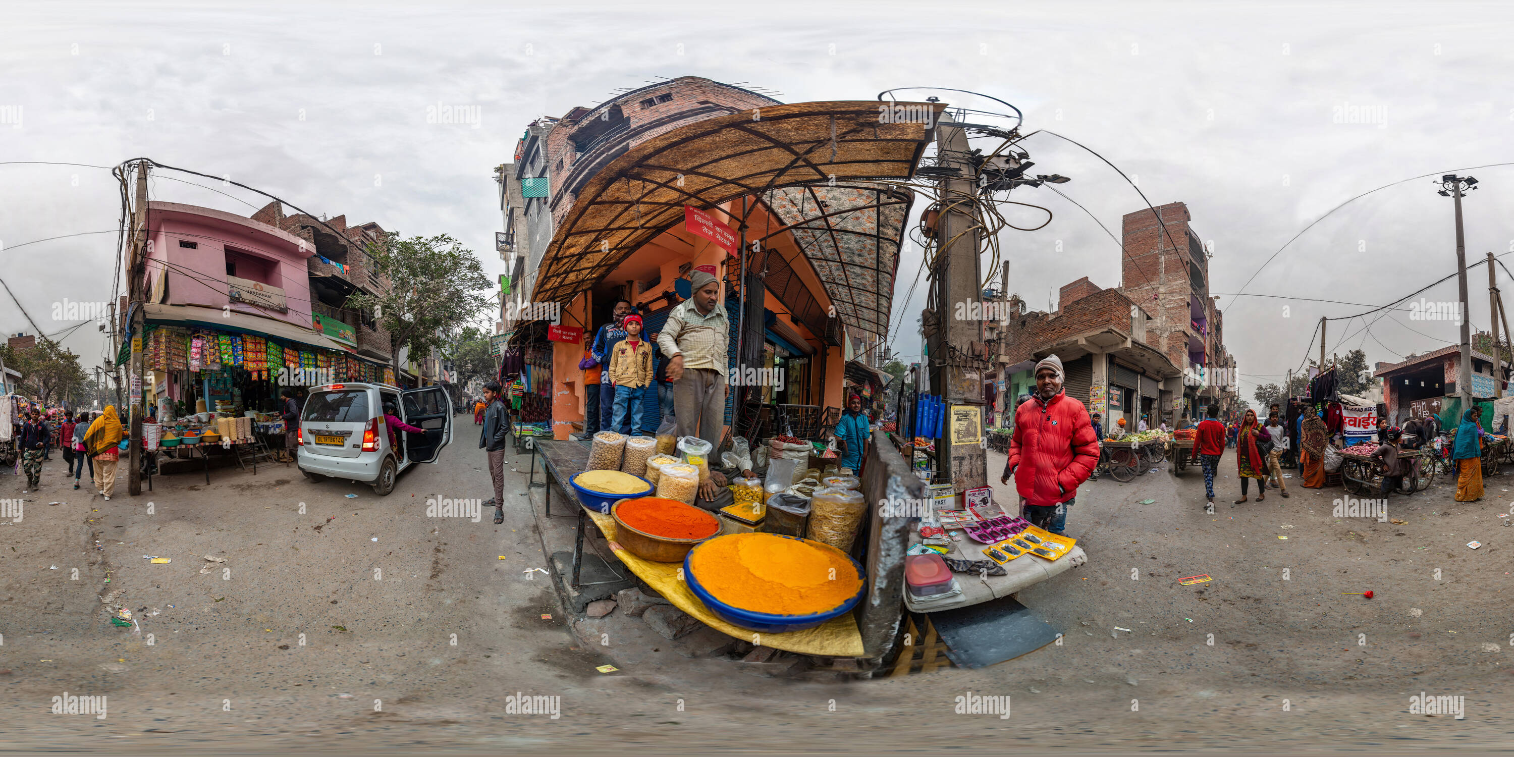 360 degree panoramic view of 360 View showing market street with a corner spice shop in Sabji Mandi Road in slum resettlement colony of JJ Colony Madanpur Khadar, New Delhi, India