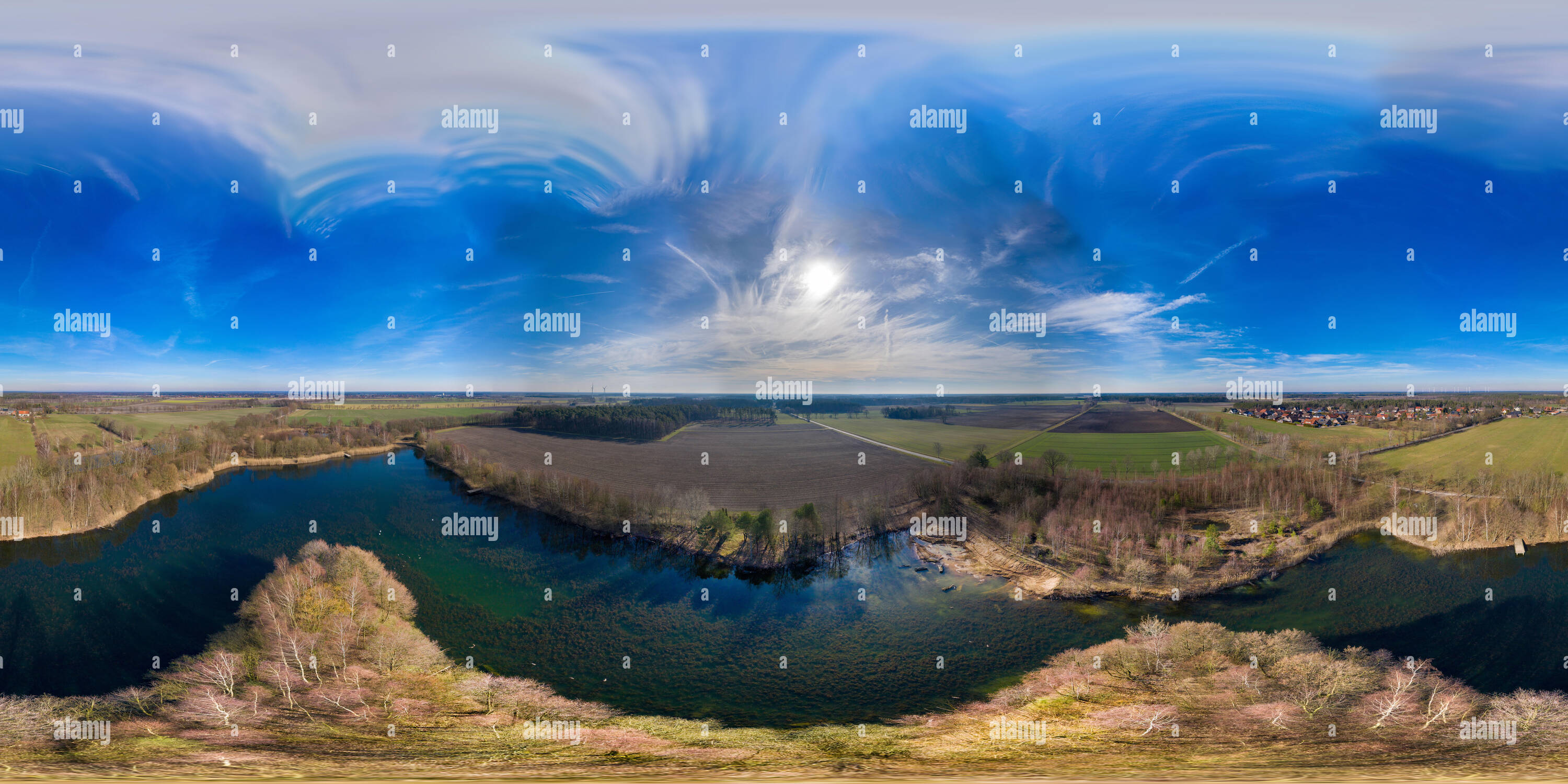 Aerial Spherical panorama from a fishing lake in northern Germany, over a small island in a pond covered with forest, flight height 40 meters - Stock Image