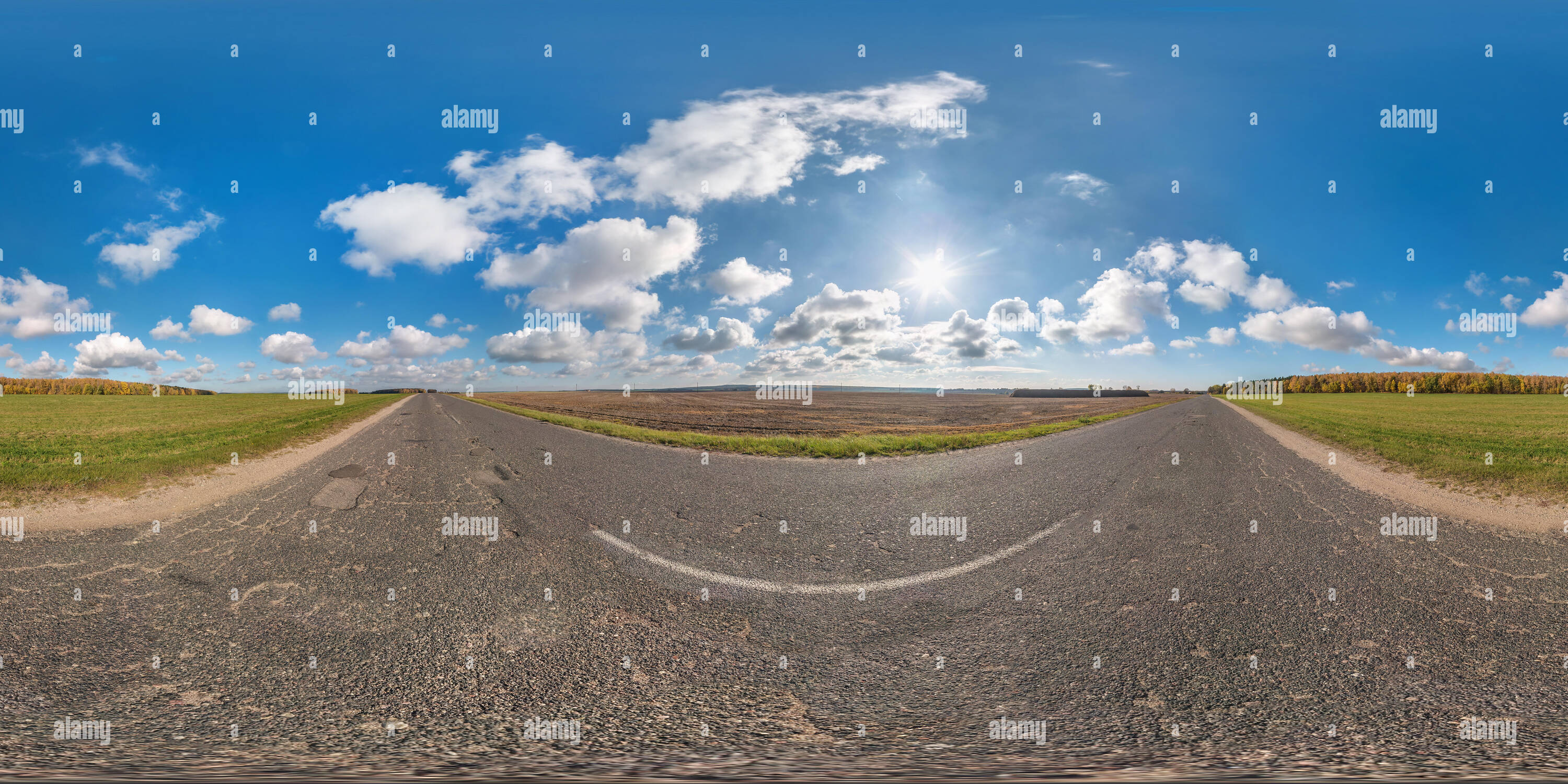 Full spherical seamless panorama 360 degrees angle view on no traffic asphalt road among fields in sunny day with awesome clouds. 360 panorama in equi - Stock Image